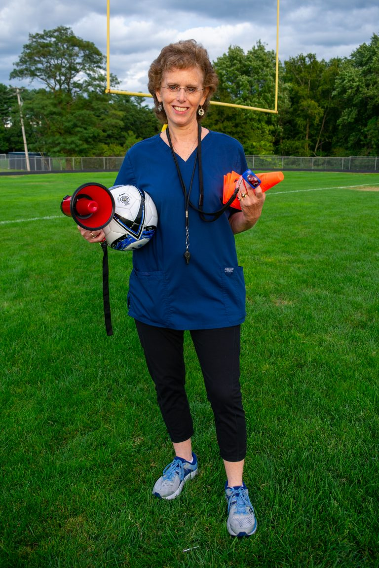 Sharon Frank on a football field holding a bullhorn, soccer ball, pulse oximeter, and orange cones